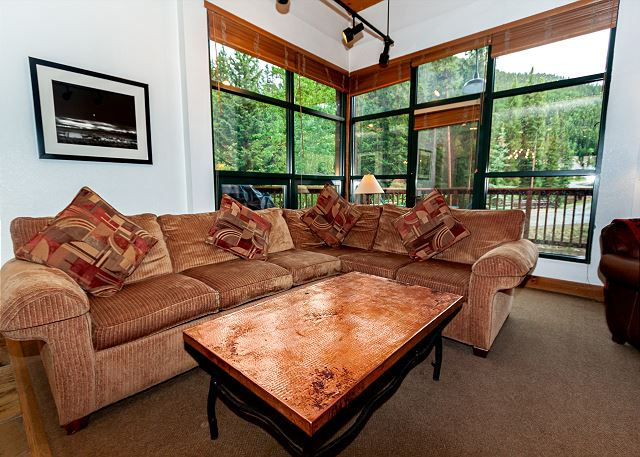 The living area features a gas fireplace, a large flat screen TV, and access to the large private deck.