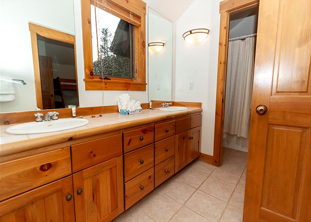 The upstairs jack-and-jill bathroom features a double sink vanity.