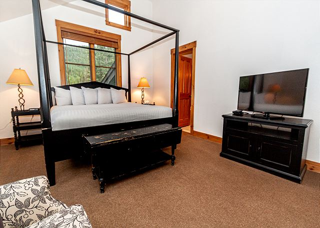 The master bedroom features a king bed, vaulted ceilings, and a flat screen TV.