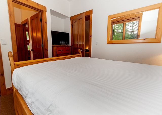 The first upstairs guest bedroom features a queen bed, flat screen TV,  and a jack-and-jill bathroom.