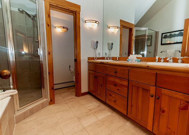 The master bathroom features a double sink vanity, walk-in shower, and a jetted soaking tub.