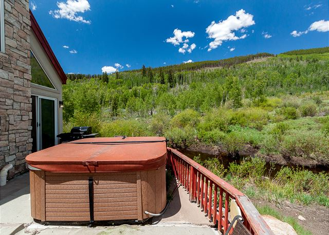 The large, private deck offers beautiful views, a private hot tub, and a gas grill.
