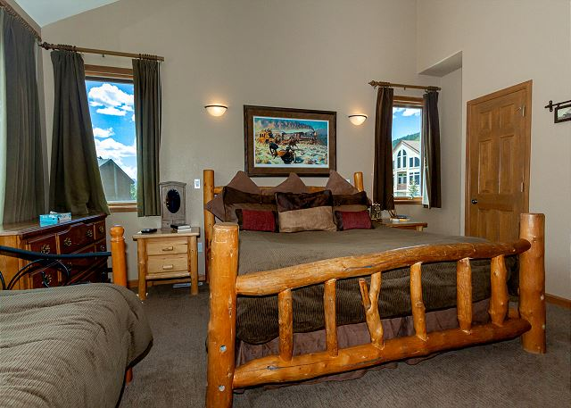The master bedroom features a king bed, a day bed, and mounted flat-screen TV.