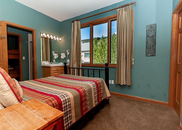 The upstairs guest bedroom features a queen bed and vanity in the room to free up space in the jack-and-jill bathroom.