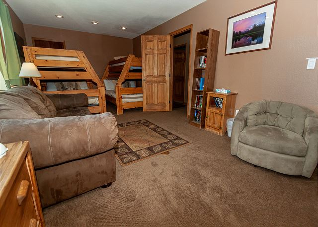 The lower guest bedroom features a large seating area with a fireplace and two twin-over-full bunk beds.