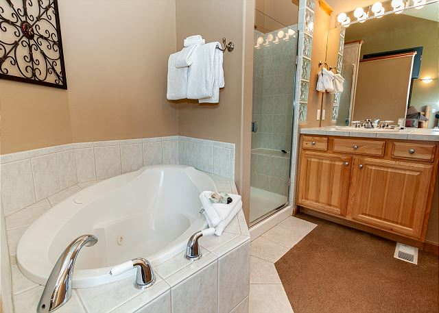 The master bathroom features a walk-in shower, two vanities, and jetted tub.