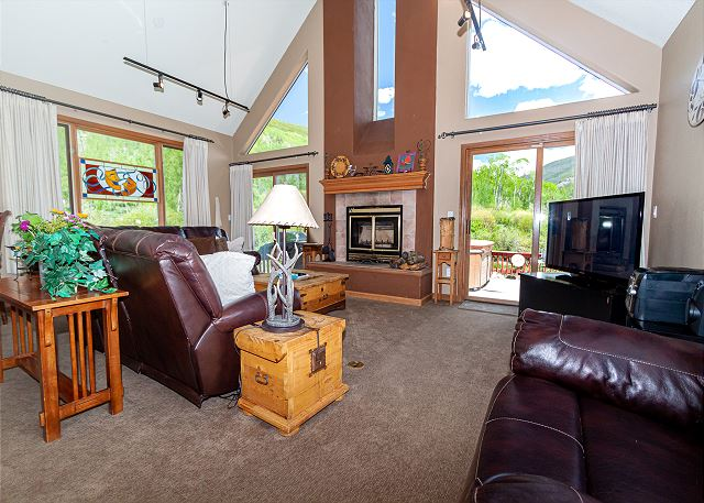 The living area features vaulted ceilings, views of the mountains on three sides, ample seating, and a wood-burning fireplace.