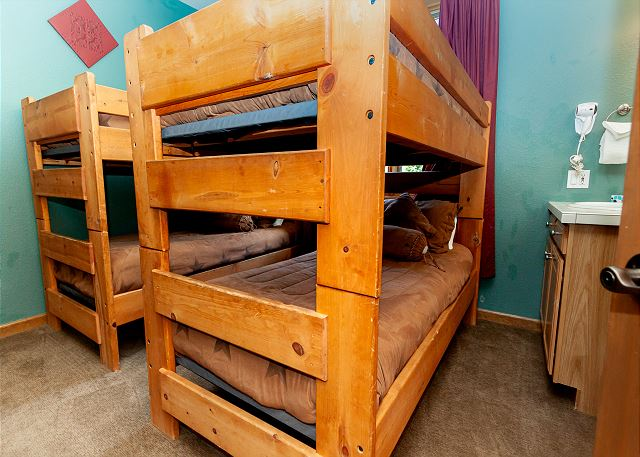 Upstairs guest bedroom with two bunk beds and vanity in the room.