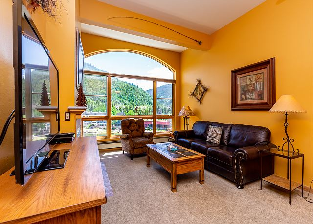 The living area features a gas fireplace, flat screen TV, and spectacular views.