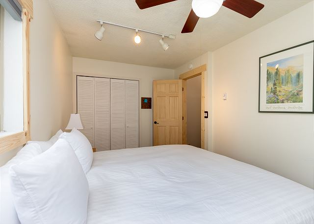 The first bedroom features a king bed with our Ivory White bedding and a mounted flat screen TV.