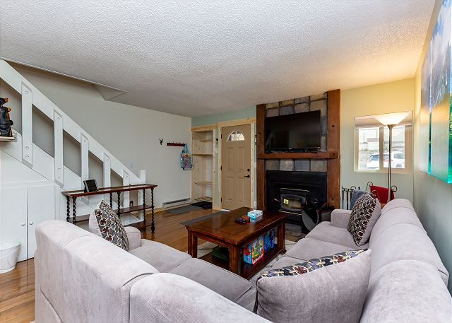 The living area features comfortable seating, a wood-burning fireplace, and a mounted flat screen TV. The entryway has hooks and storage shelves to store your gear as you come and go throughout the day.