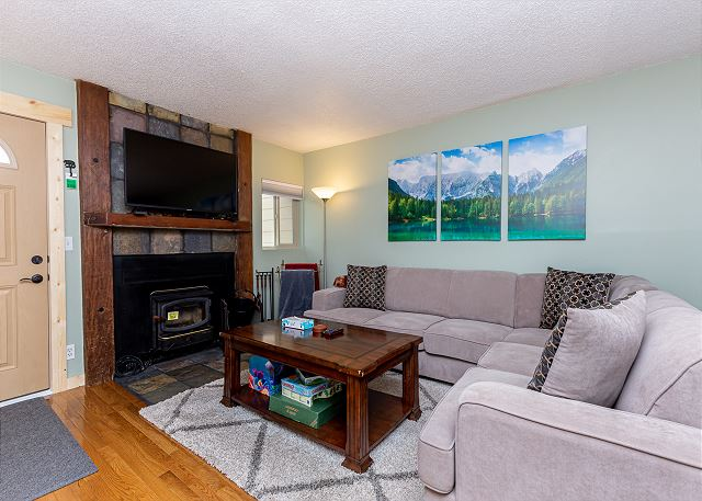 The living area features comfortable seating, a wood-burning fireplace, and a mounted flat screen TV.