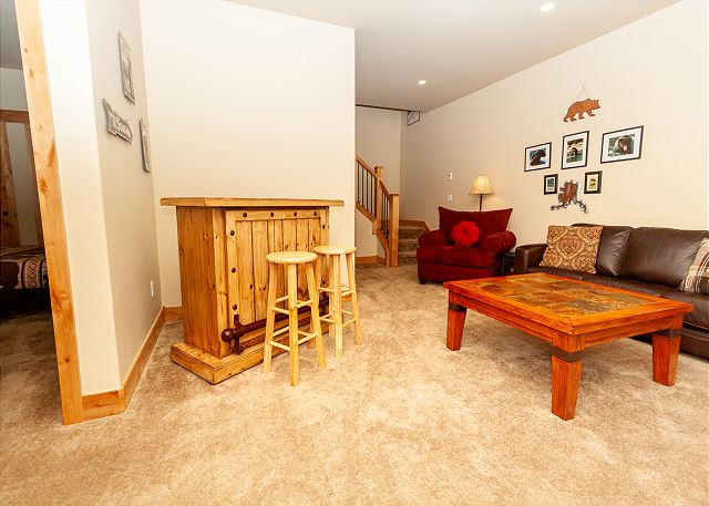 The den is downstairs and features a flat-screen TV, a bar with 2 stools, and access to the walk-out patio.