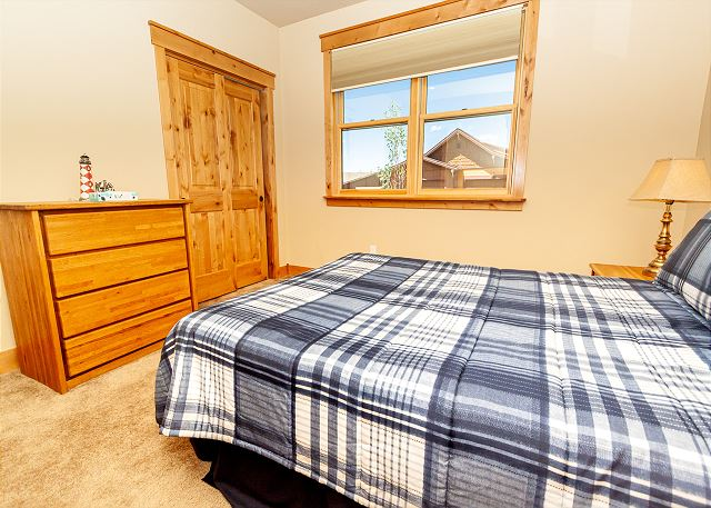 The first guest bedroom features a queen bed and private access to the downstairs bathroom.