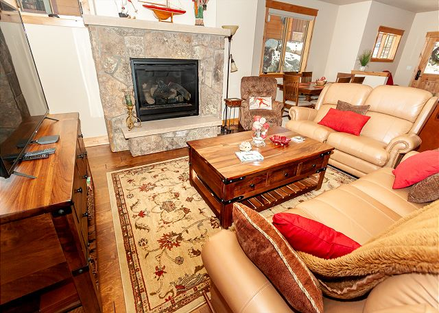 The living area features a flat-screen TV, a gas fireplace, and access to the private balcony.