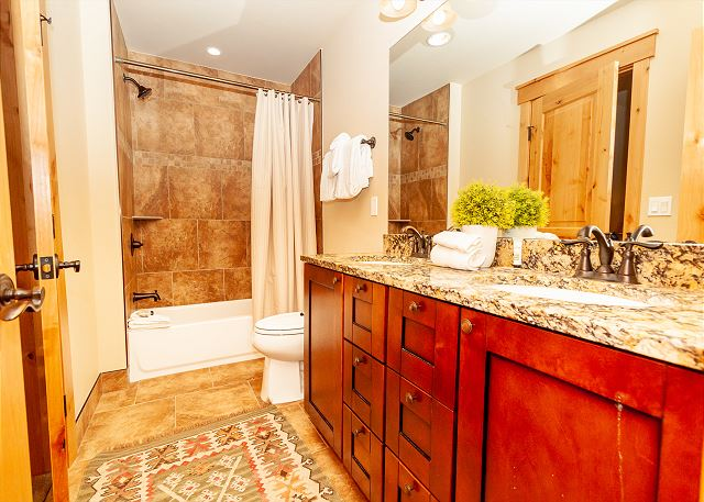 The downstairs bathroom features a double sink vanity with granite countertop, and a shower-tub combination.