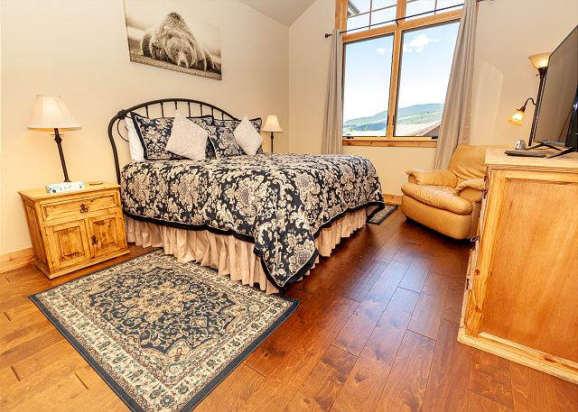 The master bedroom is on the main level, just off the living area. It features a flat-screen TV, a king bed, and a seating area.