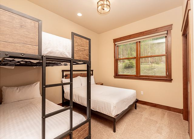 The second guest bedroom features a queen bed and a twin-over-twin bunk bed.