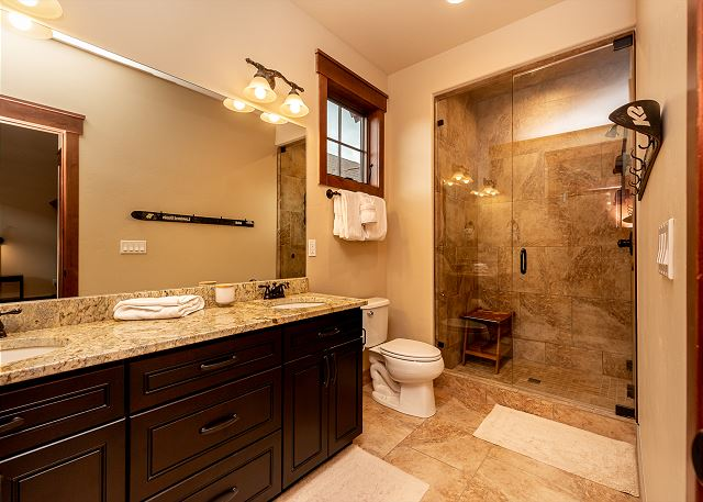 The master bathroom features a double sink vanity and a walk-in shower.