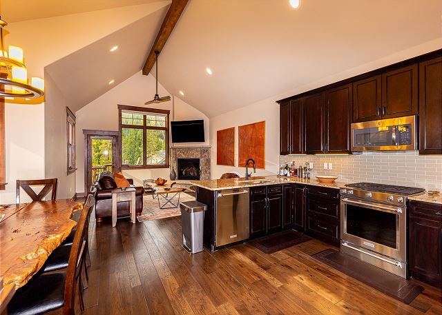 The kitchen features granite countertops, stainless steel appliances, and a breakfast bar.