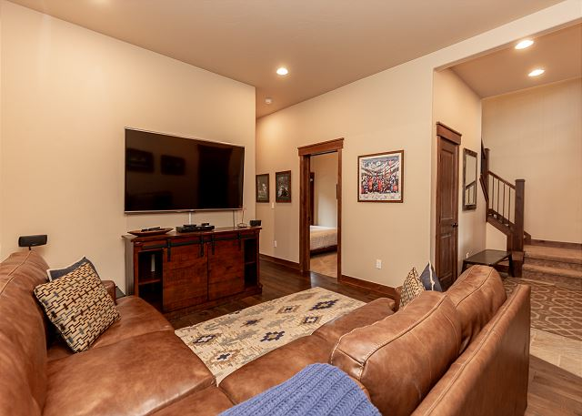 The den is downstairs. It features access to the patio, a flat-screen TV, and a comfortable sectional sofa.