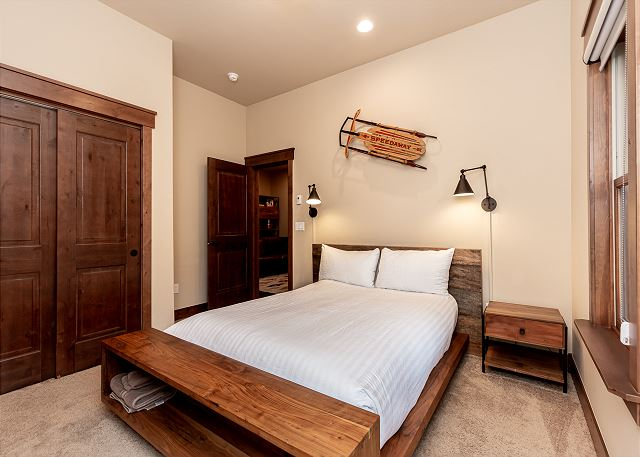 The first guest bedroom features a queen-sized bed and access to the patio.