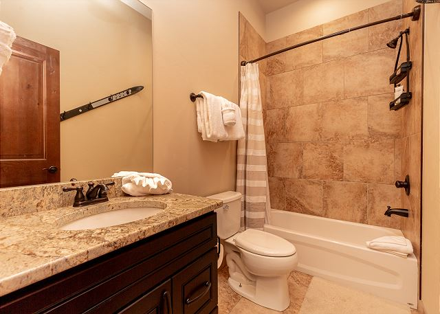 The downstairs guest bathroom features a vanity with a granite countertop and a shower-tub combination.