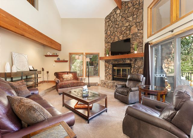 The living area features vaulted ceilings, a gas fireplace, a mounted flat screen TV and an inviting seating area.