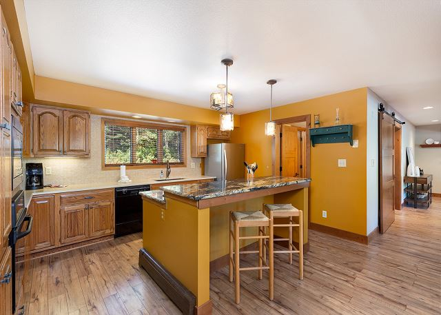 The kitchen features granite countertops, stainless steel appliances and a breakfast bar.