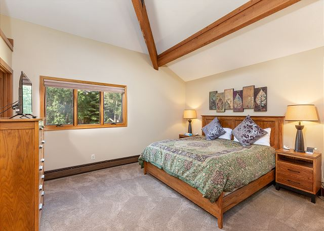 First master bedroom has a king sized bed , a flat screen TV and vaulted ceilings.