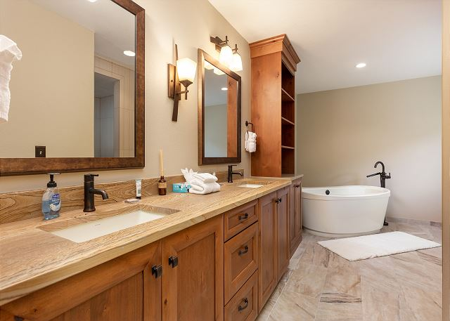 The first master bathroom has a spa-like feel with granite countertops, spacious double sink vanity, a soaking tub, and a walk-in shower with a bench.