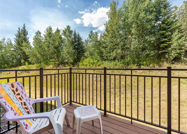 The deck off first guest bedroom has seating and treed views.