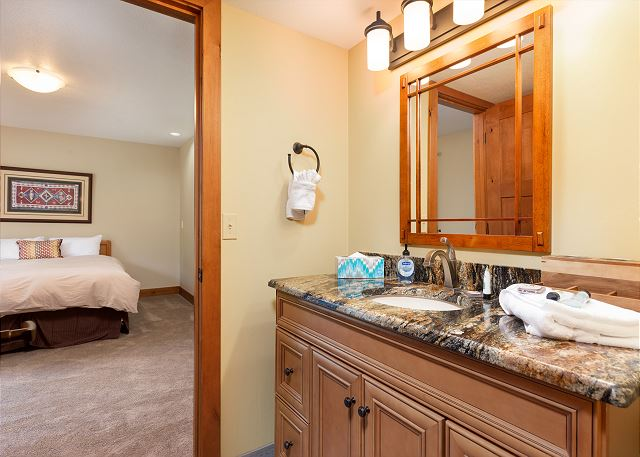 Main level bathroom has granite countertops and is accessed through the first guest bedroom.