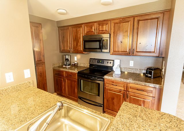 The kitchen features granite countertops and stainless steel appliances.