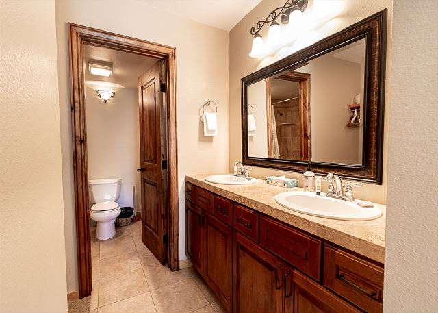 The master bathroom features a double sink vanity with granite, and a separate toilet and tub area.