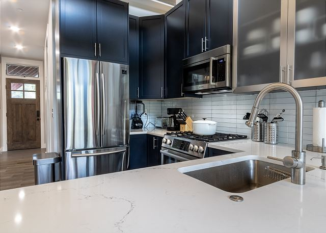 The kitchen features stainless steel appliances, granite countertops, and custom cabinetry.