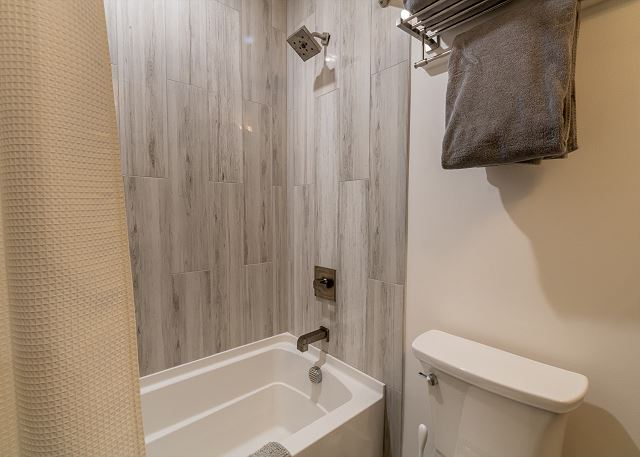 The guest bedroom has a vanity with granite countertops and a shower/tub combination.