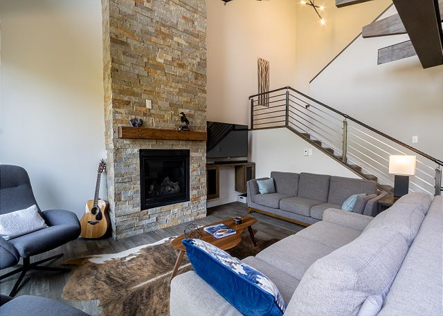 The living area features a gas fireplace with stone surround, a flat screen TV, and vaulted ceilings.