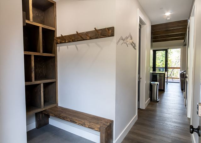 The entryway has hooks, a bench, and cubbies for convenient storage.