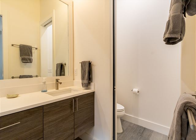 The master bathroom features a luxurious walk-in shower, a double sink vanity with granite countertop, and separate toilet area for added privacy.