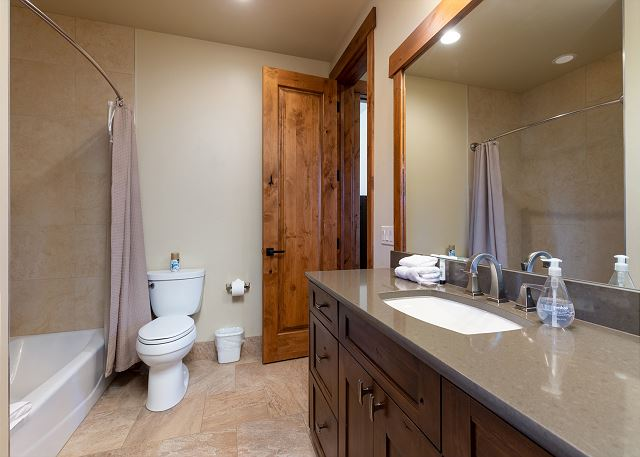 The first guest bathroom features a vanity with granite countertop and a shower/tub combination. It can be accessed from the first guest bedroom and the den.