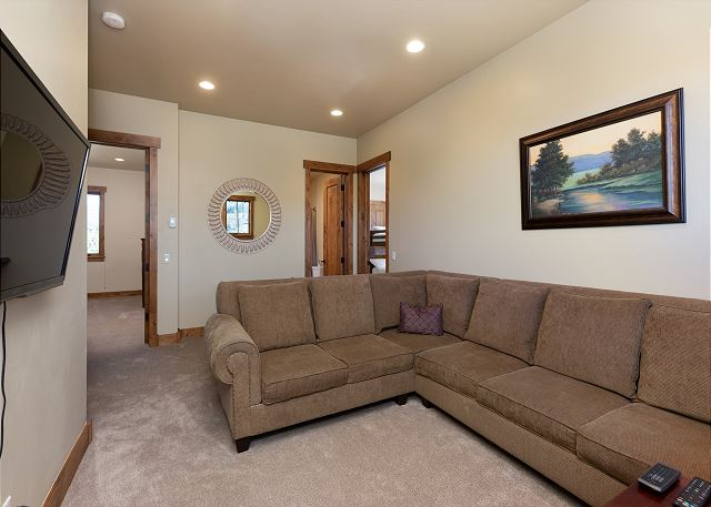 The sitting area is upstairs and features a large sectional sofa and a smart TV. It has access to the first guest bathroom.