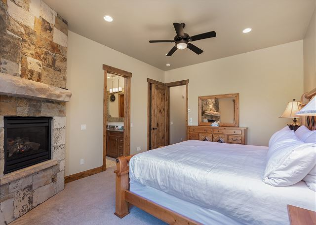 The master bedroom is on the main level and features a king bed, it's own fireplace and private access to the back yard.