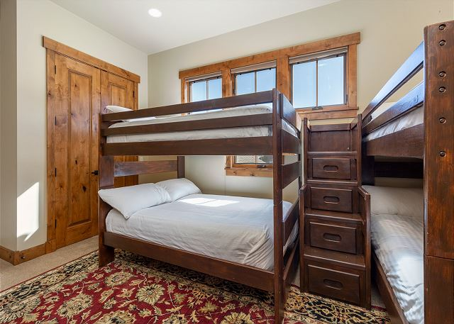 The second guest bedroom features two full-over-full bunk beds, a smart TV, and an en-suite bathroom.