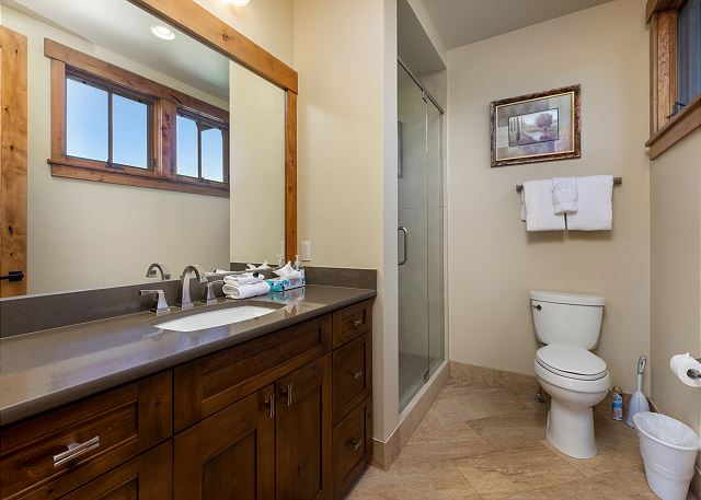 The second guest bathroom is en-suite to the second guest bedroom and features a vanity with a granite countertop and a walk-in shower.