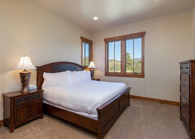 Upstairs is the first guest bedroom. It features a king bed and private access to the first guest bathroom.