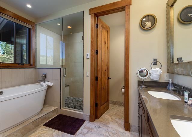 The master bathroom features a double sink vanity with granite countertop, a soaking tub and walk-in shower.