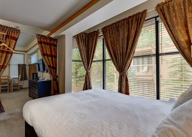The bedroom area has a curtain for added privacy and features a queen-sized bed and beautiful views from the large windows.