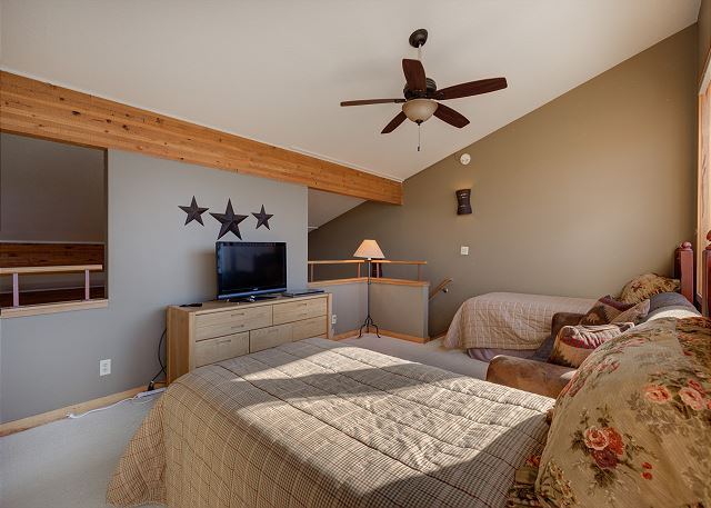 The second guest bedroom is in the upstairs loft, and features two twin-sized beds, a queen-sized sleeper sofa and a flat screen TV.