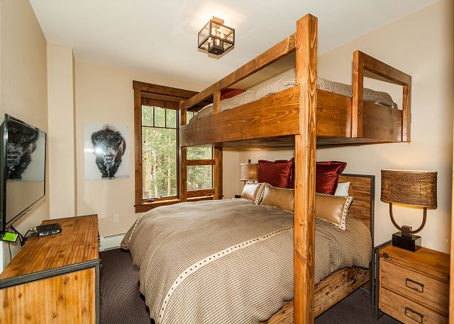 The guest bedroom features a full-over-queen bunk bed and a flat screen TV.
